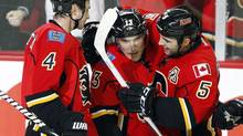 Calgary Flames' Michael Cammalleri, centre, celebrates his hat-trick goal with teammates Jay Bouwmeester, left, and Mark Giordano during third period NHL action against the Dallas Stars in Calgary on Wednesday, Feb. 13, 2013. The Calgary Flames beat the Dallas Stars 7-4. (Jeff McIntosh/THE CANADIAN PRESS)