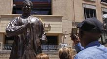 People take photos of the giant statue of former president Nelson Mandela, in Mandela Square, Johannesburg, Dec. 9, 2012. (Denis Farrell/AP)