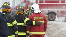 Fire Chief Yvan Charron, right, walks up to the scene at Résidence du Havre with fellow firefighters on Jan. 25, 2014, in L'Isle-Verte, Que. (Cole Burston For The Globe and Mail)