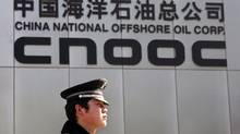 A security officer stands outside the headquarters of China National Offshore Oil Corp (CNOOC) in Beijing. (CLARO CORTES IV/REUTERS)
