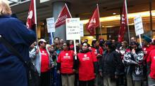 Unifor workers rally in front of Cadillac Fairview headquarters in Vancouver on Oct. 31, 2013, to support 150 cleaners who face layoffs from their jobs at two downtown office buildings. (Wendy Stueck/The Globe and Mail)