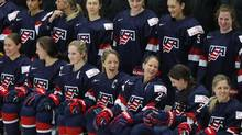 United States hockey captain Meghan Duggan laughs with Kacey Bellamy during a team photo on March 30, 2017. (Paul Sancya/AP)