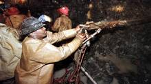 A miner drills into a rock face in a South African gold mine in this file photo. The country's mining sector needs investment in infrastructure to keep up with its rivals. (Peter Andrews/Reuters/Peter Andrews/REUTERS)