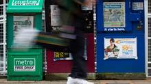 A man runs past newspaper boxes in downtown Vancouver. A new report suggests that the Canadian newspaper industry will have to contend with revenues that continue to shrink over the next four years. (DARRYL DYCK For The Globe and Mail)