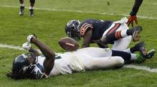 Seattle Seahawks wide receiver Sidney Rice, left, lies on the field after a hard hit by Chicago Bears safety Major Wright on his game-winning touchdown reception in overtime of an NFL football game in Chicago, Sunday, Dec. 2, 2012. The Seahawks won 23-17 in overtime. (Charles Rex Arbogast/AP)