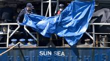 RCMP officers cover the the stern of a ship filled with Tamils from Sri Lanka. The ship carrying 490 suspected asylum seekers docked at Canadian Forces Base Esquimalt near Victoria Aug. 13, 2010. (John Lehmann/The Globe and Mail/John Lehmann/The Globe and Mail)