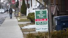 A for-sale sign staked into the front lawn of a Toronto house. (Kevin Van Paassen/The Globe and Mail)