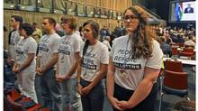 Protesters stand up as Canadian Environment Minister Peter Kent speaks at the climate conference in Durban, South Africa, on Wednesday. (Malkolm Boothroyd/Associated Press)