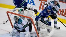 Vancouver Canucks' Henrik Sedin tangles with San Jose Sharks' Marc-Edouard Vlasic, right, and Justin Braun behind goalie Antti Niemi, of Finland, during the second period in game 1 of an NHL Western Conference quarter-final playoff hockey series in Vancouver, B.C., on Wednesday May 1, 2013. (The Canadian Press)