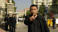 A plain-clothes policeman tries to stop photos being taken outside the house of the wife of jailed Chinese Nobel Peace laureate Liu Xiaobo in Beijing on Oct. 13, 2010. (PETER PARKS/AFP)