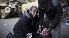 An injured anti-government protester is administered first aid in front of army vehicles during clashes in Tahrir, or Liberation square, in Cairo, Egypt, Wednesday, Feb. 2, 2011. (Tara Todras-Whitehill/Tara Todras-Whitehill/AP)