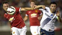 Manchester United defender Jonny Evans, left, and Los Angeles Galaxy forward Robbie Keane battle for the ball during the first half at Rose Bowl.