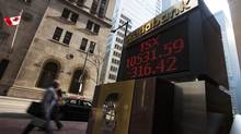 People walk by a sign displaying TSX information in Toronto, August 2009. (MARK BLINCH/Mark Blinch/Reuters)