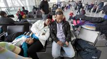 Nayajah Bardalo, 4, sleeps beside mom, Nicole Speed, with dad, Wayne Bardelo, waiting for their delayed flight. (Deborah Baic/The Globe and Mail)