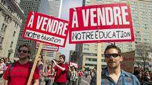 "Students hold signs during a protest against tuition hikes in downtown Montreal, Quebec March 22, 2012. The signs read ""For sale our education"". (CHRISTINNE MUSCHI/REUTERS/CHRI"