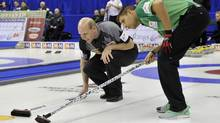 Skip Kevin Martin, left, and skip John Morris check on ice conditions during draw 14 at the Roar of the Rings Canadian Olympic Curling Trials in Winnipeg, December 6, 2013. (FRED GREENSLADE/REUTERS)