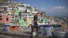 """In this March 21, 2013 photo, Nicolas Richnado watches over buckets filled with water as he waits for his mother to return from carrying a bucket of water to their home in Jalousie, a cinder block shantytown recently painted in colors in Petionville, Haiti. A $1.4 million effort titled """"Beauty versus Poverty: Jalousie in Colors"""" is part of a project to relocate people from the displacement camps that sprouted up after Haiti's 2010 earthquake. (Dieu Nalio Chery/The Associated Press)"""