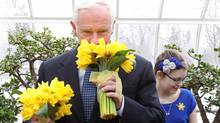 Governor General David Johnston sniffs a bouquet of daffodils he received from cancer patient Sarah Telford, 12, to mark the beginning of the Canadian Cancer Society's Daffodil Days at Rideau Hall in Ottawa on, March 17, 2011. THE (Patrick Doyle/The Canadian Press/Patrick Doyle/The Canadian Press)