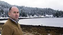 Ellis Ross, chief councillor of the Haisla First Nation, on the shores of Douglas Channel with the Kitamaat Village dock in the background, Kitamaat Village, B.C. (Robin Rowland for The Globe and Mail)