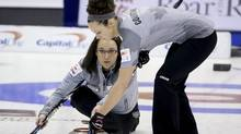 Skip Val Sweeting (L) of Team Sweeting throws a rock as third Joanne Courtney sweeps during draw five against Team Jones at the Roar of the Rings Canadian Olympic Curling Trials in Winnipeg, Manitoba December 2, 2013. (Reuters)