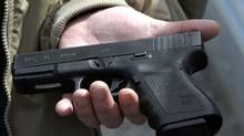 Roanoke Firearms owner John Markell holds a Glock 9 mm pistol in Roanoke, Va. The gun is similar to the one sold in his gun shop to Cho Seung-Hui, who killed 32 people at Virginia Tech in 2007. (Don Petersen/AP)