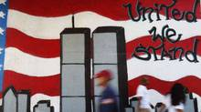People walk past a mural in the Queens borough of New York honouring victims of the Sept.11, 2001, attacks on the World Trade Center. (SHANNON STAPLETON/Reuters)