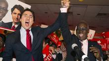 Liberal Leader Justin Trudeau, left, raises the arm of Emmanuel Dubourg in Montreal on Nov. 25, 2013, following Mr. Dubourg's win in federal by-election for the riding of Bourassa. The latest Canadian Press Harris-Decima survey indicates Liberal support is at 34 per cent, while the Conservatives tally support of 26 per cent. (Graham Hughes/The Canadian Press)
