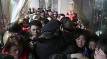 A police officer stops residents from rushing into a real estate trading centre in Shanghai, March 5, 2013. China's plans to curb property speculation are likely to be more bark than bite, and markets have overreacted because of the uncertainty over how local governments will implement measures including a 20 per cent capital gains tax on house sales. (STRINGER/CHINA/REUTERS)