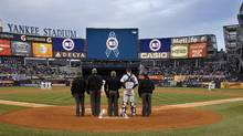 Members of the New York Yankees and the umpires bow their heads during a moment of silence for those killed in a bomb blast at the Boston Marathon on April 15, before their MLB Interleague game with the Arizona Diamondbacks at Yankee Stadium in New York April 16, 2013. Players are all wearing the number 42 in honor of Hall of Fame player Jackie Robinson. (Ray Stubblebine/Reuters)