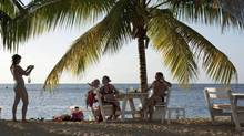 Tourists pose for a picture on the beach in Samana, Dominican Republic. (EDUARDO MUNOZ)