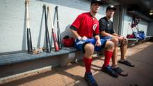 Vancouver Canadians' pitchers and Toronto Blue Jays' prospects Shane Dawson, left, of Drayton Valley, Alta., and Tom Robson, of Ladner, B.C., sit in the dugout before a minor league baseball game against the Salem-Keizer Volcanoes at Nat Bailey Stadium in Vancouver, B.C., on Monday August 19, 2013. (DARRYL DYCK/THE CANADIAN PRESS)