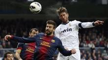 """Real Madrid's Sergio Ramos (R) heads the ball to score a goal as he is challenged by Barcelona's Gerard Pique during their Spanish first division """"classic"""" match at the Santiago Bernabeu stadium in Madrid March 2, 2013. (PAUL HANNA/REUTERS)"""