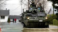 Soldiers from the 22nd Regiment, known as the VanDoos, drive their light armoured vehicle through the flooded streets of Saint Blaise, Que., May 5, 2011. (Ryan Remiorz/The Canadian Press)