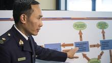 RCMP Insp. Henry Tso points to a chart as he speaks to media after a news conference in Toronto March 26, 2014. Six Ontario residents are facing charges after RCMP say thousands of investors and the Canadian government lost millions of dollars in an alleged fraudulent investment scheme. (Chris Young/THE CANADIAN PRESS)