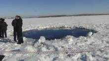 Russian police work near an ice hole, said by the Interior Ministry department for Chelyabinsk region to be the point of impact of a meteor seen earlier in the Urals region, at lake Chebarkul some 80 kilometers west of Chelyabinsk February 15, 2013. (Handout/Reuters)
