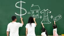 A family learning about money by drawing financial goals. (Tomwang112/Getty Images/iStockphoto)