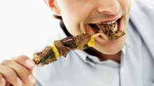 close-up of a young man eating a piece of meat from a skewer (Thinkstock)