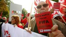 Members of the Swiss UNIA workers union display red cards during a protest in front of the headquarters of soccer's international governing body FIFA in Zurich on Oct. 3, 2013. (ARND WIEGMANN/REUTERS)