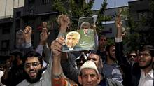Iranian worshippers chant slogans in support of supreme leader Ayatollah Ali Khamenei, and the presidential candidate Saeed Jalili, shown in the posters, in Tehran on Friday, May 31, 2013. (Ebrahim Noroozi/Associated Press)