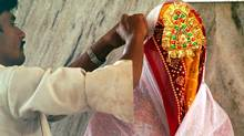A relative adjusts the veil of an unidentified bride at Jalpa Mata temple in Rajgarh, northwest of Bhopal, India, in this file photo from 2006. (PRAKASH HATVALNE/AP)