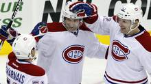 Montreal Canadiens' David Desharnais, , left, and Mathieu Darche, right, celebrate a goal by Erik Cole, center, during the third period of an NHL hockey game against the New Jersey Devils in Newark, N.J., Saturday, Dec. 10, 2011. Canadiens won 2-1. (AP Photo/Mel Evans) (Mel Evans/AP)