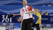 Canada's skip Kevin Koe (front) reacts as he watches a shot next to Sweden's lead Christoffer Sundgren in the semi-final of their World Men's Curling Championships in Beijing April 5, 2014. (CHINA DAILY/REUTERS)