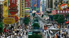 Shoppers crowd under huge signs along Shanghai's bustling Nanjing Road August 3, 2001. (Claro Cortes IV/Reuters/Claro Cortes IV/Reuters)