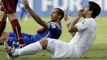 In this June 24, 2014 file photo, Uruguay's Luis Suarez holds his teeth after biting Italy's Giorgio Chiellini's shoulder during the group D World Cup soccer match between Italy and Uruguay at the Arena das Dunas in Natal, Brazil. On Thursday, June 26, 2014, FIFA banned Suarez for 9 games and 4 months for biting his opponent at the World Cup. (Ricardo Mazalan/AP)