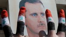 Two men with the fingers painted in the colours of the Syrian flag show the V-sign as they pose in front of a huge image of President Bashar al-Assad during a rally by thousands supporters for their leader who is facing unprecedented domestic pressure amid a wave of dissent, in central Damascus on March 29, 2011. (ANWAR AMRO/Anwar Amro/AFP/Getty Images)