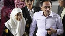 Malaysia's opposition leader Anwar Ibrahim (2nd R) arrives with his wife Wan Azizah (L), for the verdict in his final appeal against a conviction for sodomy, at the federal court in Putrajaya, February 10, 2015. Malaysia's highest court rejected on Tuesday Anwar's appeal against a 2014 sodomy conviction and upheld a five-year prison term that will likely end a political career marked by controversy. (STRINGER/REUTERS)