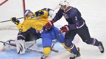 Sweden's Elias Lindholm is checked on to Team USA goaltender John Gibson by USA's Seth Jones during second period gold medal hockey action at the IIHF World Junior Championships in Ufa, Russia, on Saturday, Jan. 5, 2013. (Nathan Denette/THE CANADIAN PRESS)