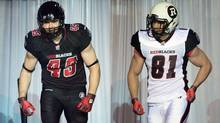 Ottawa RedBlacks CFL player John Delahunt sports the team's new home game uniform, left, while running back Patrick Lavoie sports the team's new away uniform. (The Canadian Press)