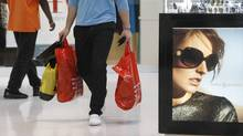A shopper carries purchases while shopping at Dolphin Mall in Miami. (Lynne Sladky/AP)
