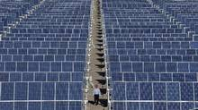 An employee walks between rows of solar panels at a solar power plant on the outskirts of Dunhuang, Gansu province. (SHENG LI/REUTERS)